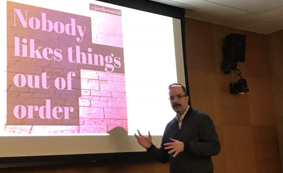 Christian Sandvig speaking at the Cornell University Communication Department, gesturing in front of the phrase