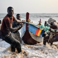 A group of men haul a boat onshore through the surf in San Pedro(Ivory Coast)